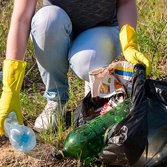 Volunteer girl in yellow gloves collects garbage selective focus